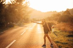 Young backpacking adventurous woman hitchhiking on the road.Stopping a car with a thumb.Travel lifestyle.Low budget traveling. Adventurous active vacations Stock Photo