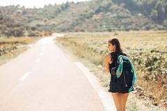 Young backpacking adventurous woman hitchhiking on the road.Traveling backpacks volume,packing essentials.Travel lifestyle Stock Photography