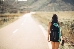 Young backpacking adventurous woman hitchhiking on the road.Traveling backpacks volume,packing essentials.Travel lifestyle Stock Photos