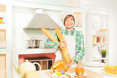 Young baker with fresh bakery food at the kitchen Royalty Free Stock Photography