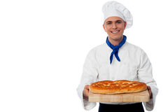 Young baker holds a loaf on breadboard Stock Photos