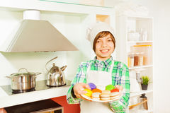 Young baker with plate of colored macaroons Stock Photo