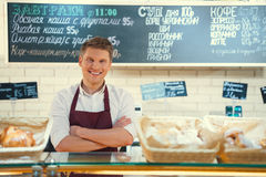 Young baker. Smiling baker on the counter Royalty Free Stock Image