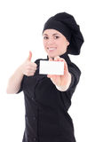 Young baker woman in black uniform showing visiting card isolate Stock Images