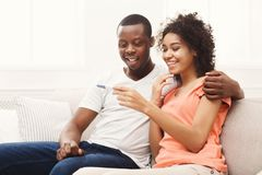 Young african-american couple happy about results of pregnancy test. Young balck couple happy about positive results of pregnancy test, hugging each other, copy stock image