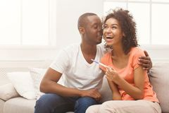 Happy african-american couple with pregnancy test. Young balck couple happy about positive results of pregnancy test, hugging each other, copy space royalty free stock photo