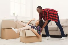 Young balck couple unpacking moving boxes. Happy african-american couple unpacking moving boxes and having fun in new apartment, copy space Royalty Free Stock Photo