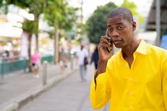 Young bald African businessman talking on phone in the city streets outdoors royalty free stock photography