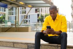 Young bald African businessman using phone while sitting outside the subway train station royalty free stock photo