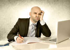 Young bald attractive business man bored with computer at work. Young bald attractive Hispanic businessman bored and tired with computer laptop working at office Royalty Free Stock Image