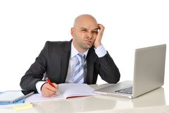 Young bald attractive business man bored with computer at work Royalty Free Stock Photos
