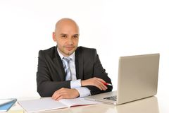 Young bald attractive business man with computer at work Royalty Free Stock Photo