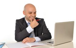 Young bald attractive business man with computer at work Royalty Free Stock Images