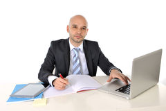 Young bald attractive business man with computer at work. Young bald attractive business man working with computer isolated on white background Royalty Free Stock Photography