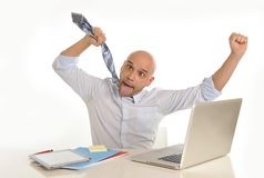 Young bald attractive business man desperate with computer at work. Young bald attractive business man in stress desperate and crazy working with computer Stock Images