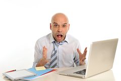 Young bald attractive business man desperate with computer at work. Young attractive business man in stress desperate and frustrated working with computer Stock Image