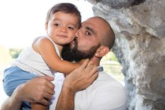 Father and son in arms lifestyle park outdoor. Young bald father and his smiling son kissing hugging and enjoying time together in father day celebration stock photography