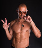 Young bald handsome man. In sunglasses with naked torso on a dark background Stock Images