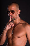 Young bald handsome man. In sunglasses with naked torso showing silence gesture with finger on his lips on a dark background Royalty Free Stock Image