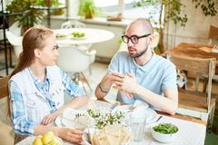 Man and young woman talking in cafe. Young bald male in glasses and female sitting at served table looking to each other and chatting in cafe Stock Photos
