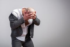 Young bald man in gray suit. A young bald man in an unbuttoned gray suit and white shirt is upset and holds his head against a white  background Royalty Free Stock Photography