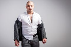 Young bald man in gray suit. A young bald man in an unbuttoned gray suit and white shirt is disheveled and upset on a white  background Stock Photos