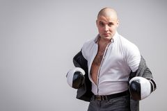 A young bald man in suit. A young bald man in an unbuttoned white shirt, gray suit and boxing gloves looks boldly into the camera, boxing on a white isolated stock photography