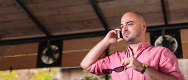 Young Bald Man Talking on the Phone - letterbox Royalty Free Stock Photography