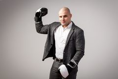 A young bald man in suit. A young bald man in a white shirt, gray suit and boxing gloves seriously looks into the camera, shows a biceps and poses on a white royalty free stock photography