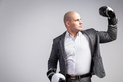 A young bald man in suit. Young bald man in white shirt, gray suit and boxing gloves showing biceps and posing on white isolated background stock image