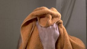 Young bald man wipes his head with a orange towel.