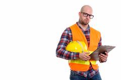 Young bald muscular man construction worker. Bald muscular man construction worker holding safety helmet and clipboard stock images