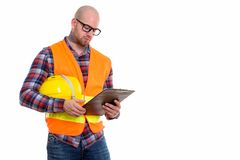 Young bald muscular man construction worker. Bald muscular man construction worker holding safety helmet and reading on clipboard stock image