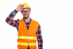 Young bald muscular man construction worker. Happy bald muscular man construction worker smiling while holding safety helmet on head stock photo