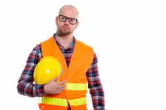 Young bald muscular man construction worker. Studio shot of young bald muscular man construction worker holding safety helmet royalty free stock image