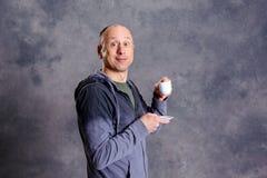 Young baldheaded man drinking coffee Stock Photos