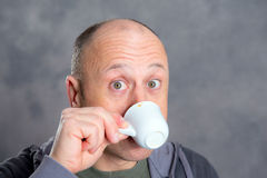 Young baldheaded man drinking coffee Royalty Free Stock Photography