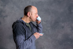Young baldheaded man drinking coffee Royalty Free Stock Image