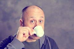 Young baldheaded man drinking coffee Stock Photo