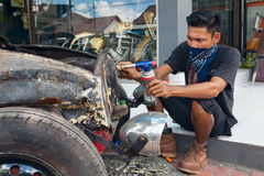 Young Balinese man renews old car Royalty Free Stock Photography