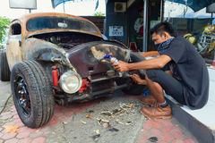 Young Balinese man renews old car Royalty Free Stock Photo