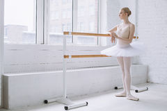 Young ballerina in ballet class. Young dreaming ballerina with a serious look at her face standing in the ballet class at the window near the barre. She is stock photo