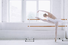 Young ballerina in ballet class. Young thin ballerina stretching at barre near big open window in ballet class. She is looking down to the floor. The girl is stock images
