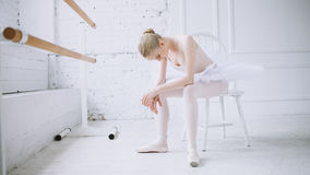 Young ballerina in ballet class. Young tired ballerina in tutu sitting on a small white chair in the big ballet class. Weary poor girl hung her head and having royalty free stock photography