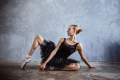 Young ballerina in a black dancing suit is posing in a loft studio. Young slim ballerina in a black dancing suit is posing in a loft studio Royalty Free Stock Image