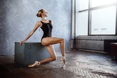 Young ballerina in a black dancing suit is posing in a loft studio. Young slim ballerina in a black dancing suit is posing in a loft studio Stock Image