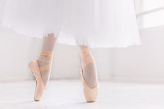 Young ballerina, closeup on legs and shoes, standing in pointe position. Young ballerina dancing, closeup on legs and shoes, standing in pointe position royalty free stock images