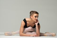 Young ballerina dancer. Beautiful young ballerina dancer sitting on a floor royalty free stock image