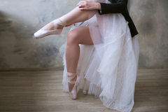 Young ballerina or dancer girl putting on her ballet shoes
