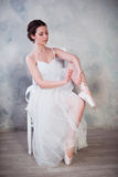 Young ballerina or dancer girl putting on her ballet shoes Stock Photo
